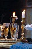 Gefüllte Sektgläser auf Tablett vor Messing-Kerzenständern mit brennenden Kerzen
