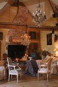 Rustikales Landhaus - Wohnzimmer - Kronleuchter über Sesseln im Rokokostil und schlichter Holztisch mit drapiertem Tischtuch vor offenem Kamin
