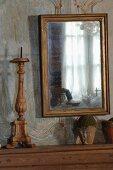 Spiegel mit Goldrahmen an verblichener Holzpaneelwand und Kerzenständer aus Holz neben Vintage Tontöpfen auf Konsole