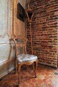 Gepolsterter Stuhl mit vergoldetem Holzrahmen im Rokokostil und Prozessionsstab an Ziegelwand in Zimmerecke