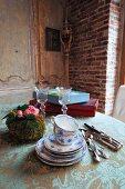 Tasse-n und Untertassenstapel mit weiss blauer Bemalung neben Silberbesteck und Blumengesteck auf Vintage Tischdecke in rustikaler Esszimmerecke