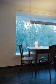 Schlichter Esstisch mit Stühlen vor festverglastem Fensterelement