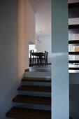 Blick von der Treppe auf den schlichten Esstisch mit Stühlen unter Pendelleuchte am Fenster