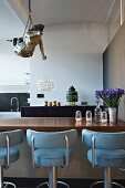 Mythical figure hanging from ceiling and bar stools with light blue upholstery at counter in open-plan loft apartment kitchen