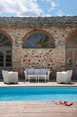 Terrasse mit weissen Outdoormöbeln und Pool vor mediterranem Haus