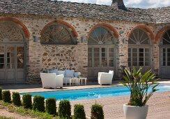 Formgeschnittene Zypressen vor Pool und Terrasse mit weisser Sitzgarnitur im Innenhof einer mediterranen Wohnanlage