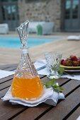 Gedeckter Terrassentisch - Erfrischungsgetränk in Kristallglaskaraffe und Glas auf weisser Stoffserviette