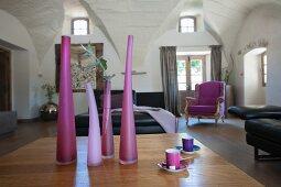 Vasen in verschiedenen violetten Farbtönen auf Tisch und schwarzes Ledersofa in grossräumigem Wohnzimmer mit Gewölbedecke