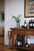 Rustikale Kommode mit verschiedenen Weinflaschen und Spirituosen