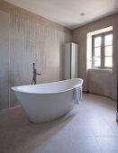 Freistehende Designer- Badewanne und Standarmatur in modernem Bad mit hellen Fliesen an Wand und Boden