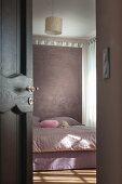 Blick durch halboffene Tür auf Doppelbett vor Raumteiler in pastellfarbenem Schlafzimmer