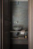 Blick durch offene Tür auf schlichte Waschschüssel auf Holzplatte an Wand in Spachteltechnik-Optik