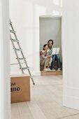 Paar sitzt im Türeingang einer neuen Wohnung mit Stehleiter und Umzugskarton