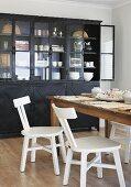 Weisse Küchenstühle mit Retro Flair an rustikalem Holztisch und Vitrine aus schwarzem Metall
