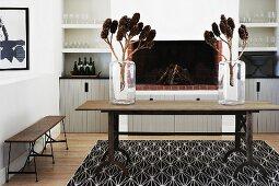 Zapfen auf Zweigen in Glasvasen auf rustikalem Holztisch vor offenem Kamin in modernem Ambiente