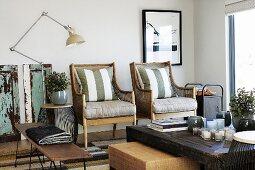 Rustikaler Couchtisch vor Sesseln mit Polstern neben Vintage Stehleuchte in modernem Ambiente