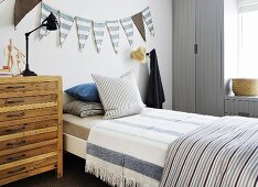 Holzkommode neben Bett mit gestreifter Bettwäsche vor Wand mit Wimpelgirlande