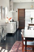Small kitchen counter, two dining tables and racing bicycle in open-plan interior