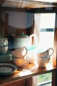 White and pastel turquoise coffee service on simple wooden shelf behind reflective glass