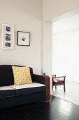 Framed pictures above retro sofa in living room