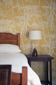Wooden bed and lamp on bedside table against floral wallpaper