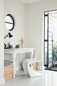 White, antique table and Panton chair in corner of room with metal-framed, industrial-style French window