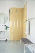 Pastel yellow, retro tiles in floor-level shower with glass partition and vintage bench in foreground