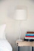 Bedside lamp with base shaped like stylised tree and stack of books on modern table with drawer