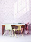 Plastic chairs in various colours at fifties-style table against wallpaper with three-dimensional pattern