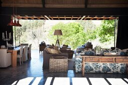 Living room terrace with floral sofa, rattan side table and dining table in background