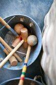 Croquet mallets and equipment in metal bucket