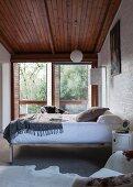 Bett mit Chrom Metallgestell an Wand neben Terrassentüren in schlichtem Schlafzimmer mit Holzdecke