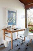 Moderner Büro Drehstuhl an Holztisch vor Wand mit aufgehängtem Bild neben Stehleuchte und offene Balkontür