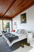 Zylinderförmiger Nachttisch neben Doppelbett in modernem Schlafzimmer mit Holzdecke