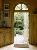 Blick in den Garten durch eine nach aussen geöffnete, verglaste Holztür; stilvolle Landhausküche in weichem Shaker-Beige
