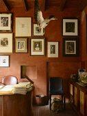 In Wischtechnik rot getöntes Arbeitszimmer mit gerahmten Schwarzweiss-Fotografien und präpariertem Vogel im Flug