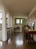 Gerahmte Bilder, an Wänden hängend und lehnend, auf umlaufender Galerie mit historischen Rundbögen zur offenen Treppenhalle