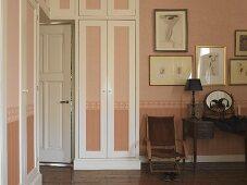 Mit Kleiderschränken umbaute Zimmertür eines stilvollen Schlafraumes; Tönung von Wand und Schranktüren in kalkigem Rose mit umlaufender Bordüre