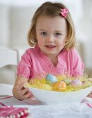 Young girl holding bowl of Easter eggs