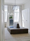 View through open door of double-sided sofa in front of white wardrobes in dressing room with traditional ambiance
