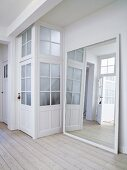 Large framed mirror leaning against wall next to doors with latticed glass panels in foyer
