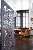 View into office with grey, metal screen; dark, exotic wood parquet floor and brown leather armchairs