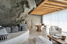 Curved bench with black and white patterned cushions against rock wall and white upholstered furniture in front of glass wall with transparent curtain