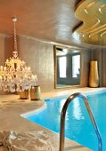 Chandelier with lit candles next to indoor swimming pool and suspended, curved golden ceiling panel