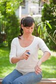 Woman spraying her arm with a spray can