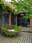 Gepflasterter Innenhof mit dekorativem Nest aus Weidenzweigen