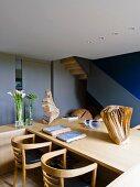 Wohnraum mit Holztisch, Armlehnstühlen & Skulpturen aus Holz