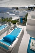 Sun loungers with blue blankets on roof terrace and view of typical, North-African architecture