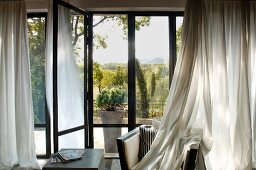 Living room with French windows leading to terrace and curtains partially draped over armchair