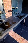 Dark stone counter with integrated sinks and strip of bright mosaic tiles in modern bathroom